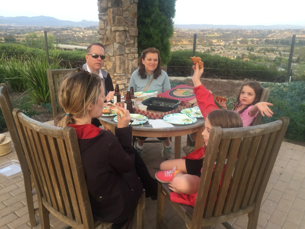 Photo description: Joy and family with Joy's parents, eating at a table in a scenic outdoor setting.