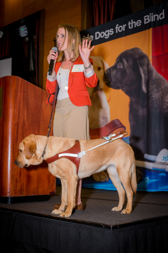 photo description: Joy speaking on stage at GDB Legacy Luncheon with Roja by her side.