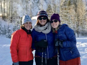 Visual Description: Joy and Jenelle with their mother, Judy, decked out in snow gear with a snowy background.