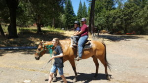 My 4 year old son riding a horse with a camp counselor while another camp counselor leads the horse at Enchanted Hills Family Camp.