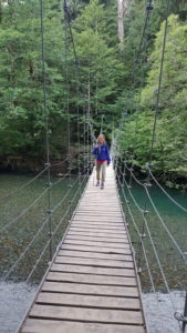 Jenelle standing on long thin suspension bridge.